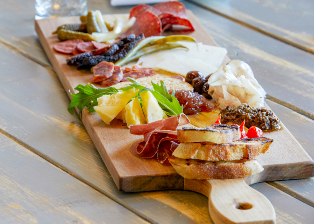 top view of charcuterie wooden board with various meat, cheese, and garnish on top of table