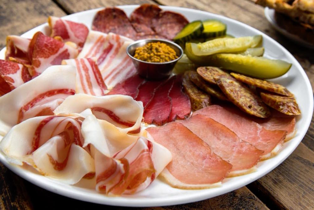 side view of charcuterie board on white plate with various meat, pickle, and mustard selection