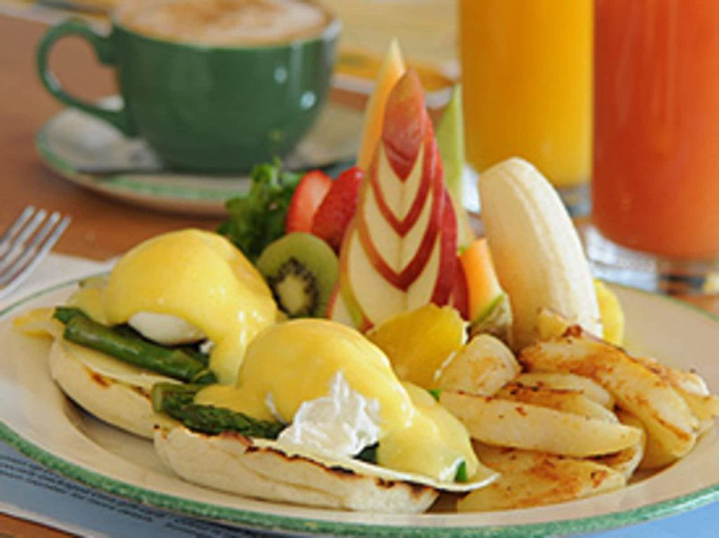 front view of brunch with eggs Benedict, fruit and hash browns on a plate in front of juice and coffee with bright colours