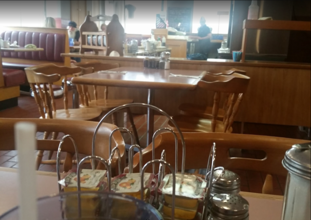 interior of breakfast restaurant with wooden furniture, tables set and windows open and bright