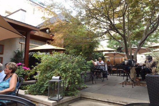 exterior patio view of restaurant with shrubs, patrons and umbrellas