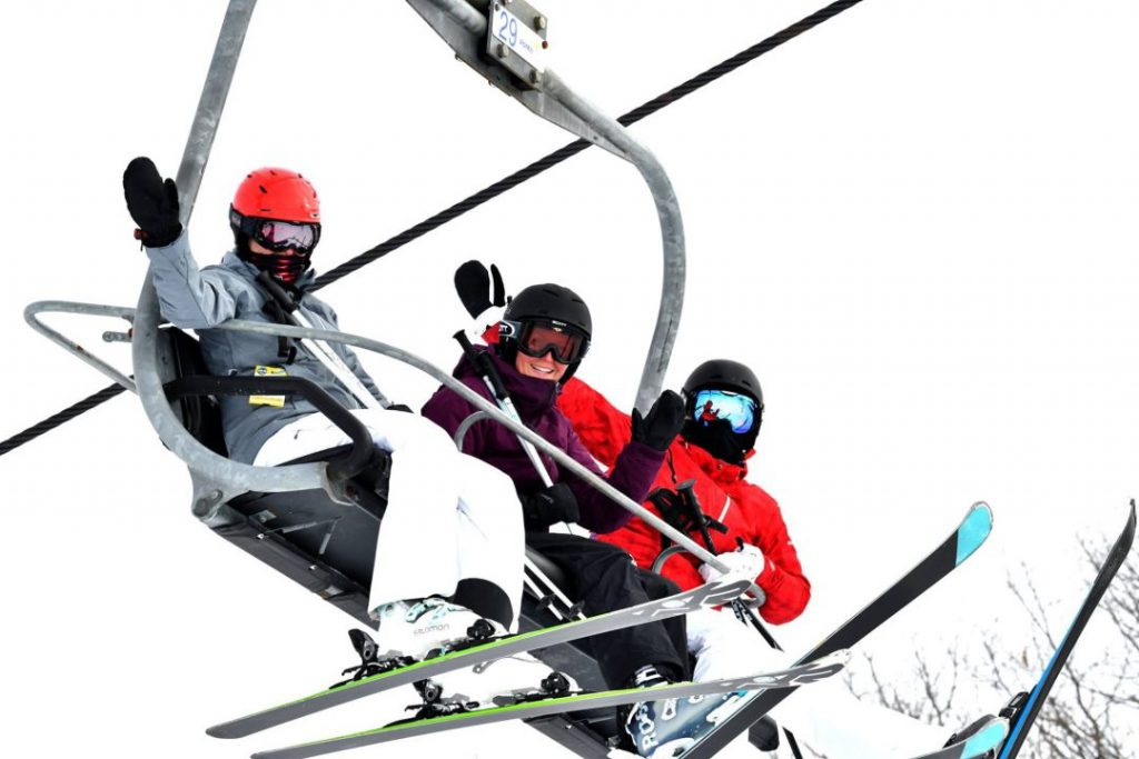 three people on ski lift waving down toward camera all wearing skis and equipment