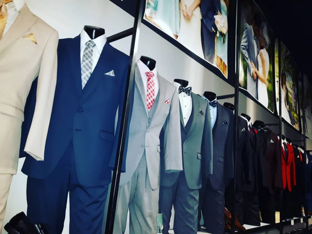 close up of mens suits hung up with tie pairings