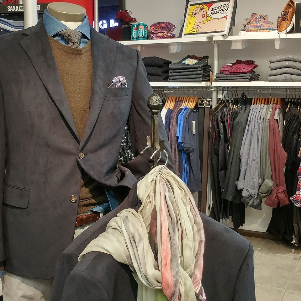 interior of menswear store with built suit on display with various jackets in behind and other product shelves