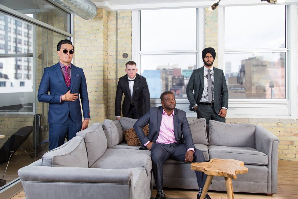 four men wearing suits in front of large windows well dressed