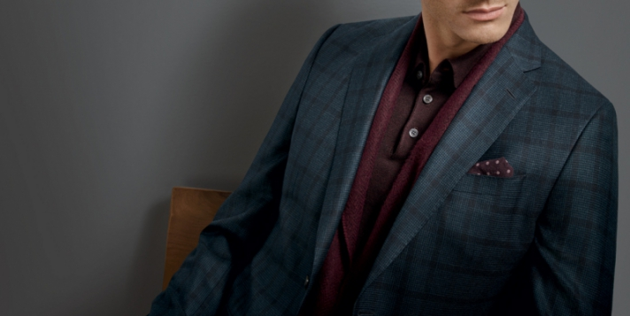 close up of mens suit without mans face in front of grey background