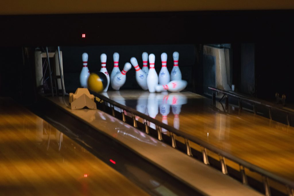 bowling lane with pins being hit by ball and gutters up