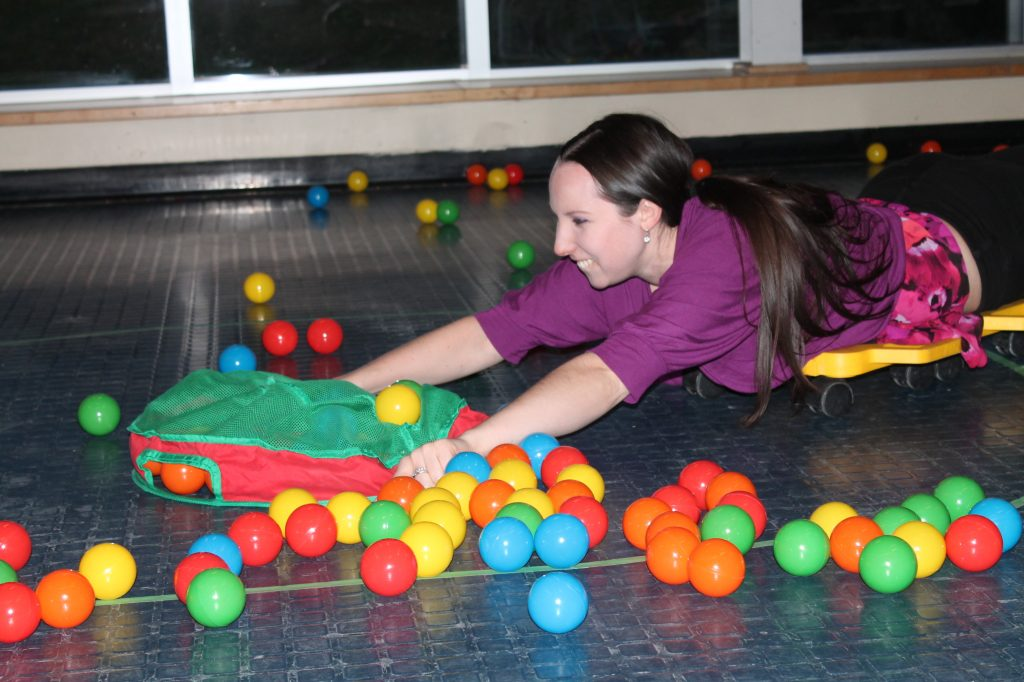 woman laying in studio type room with children's colourful play set with ball pit balls surrounding