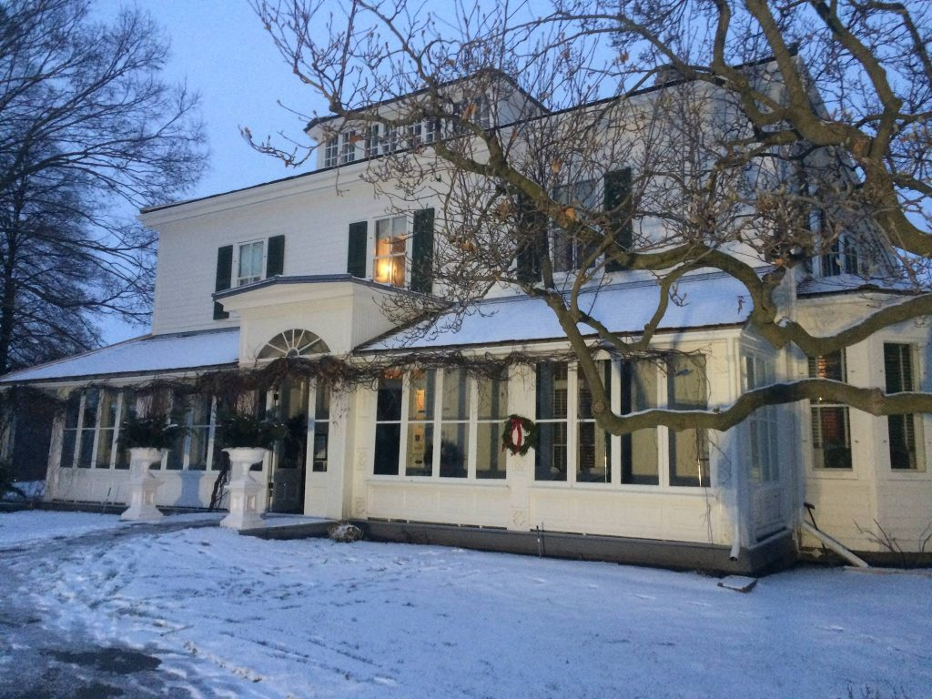exterior view of older style house with many windows on a snowy day