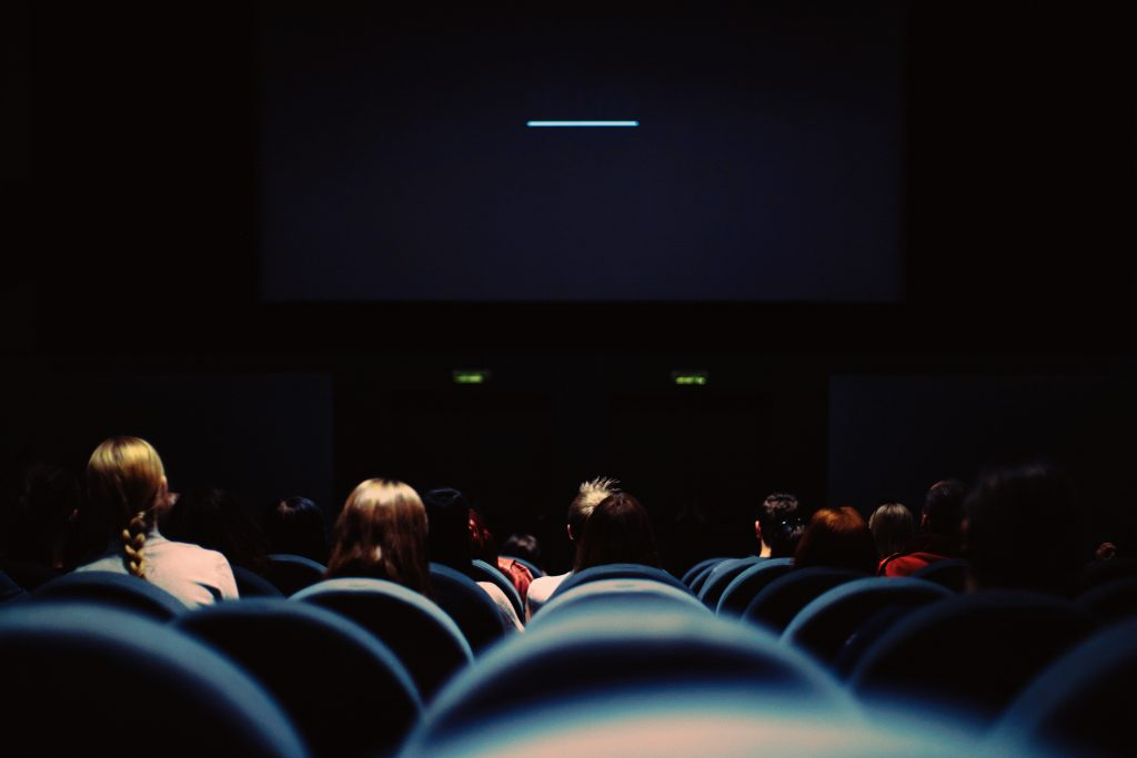 back view of movie theatre with people sitting in chairs looking towards screen in the dark