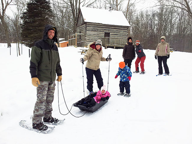 family outdoors in winter gear in front of barn style building with sleds, snowshoes and ski poles