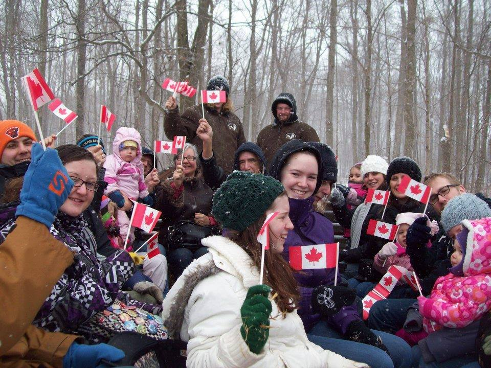 group of people in winter clothing in front of trees holding canadian flags and smiling