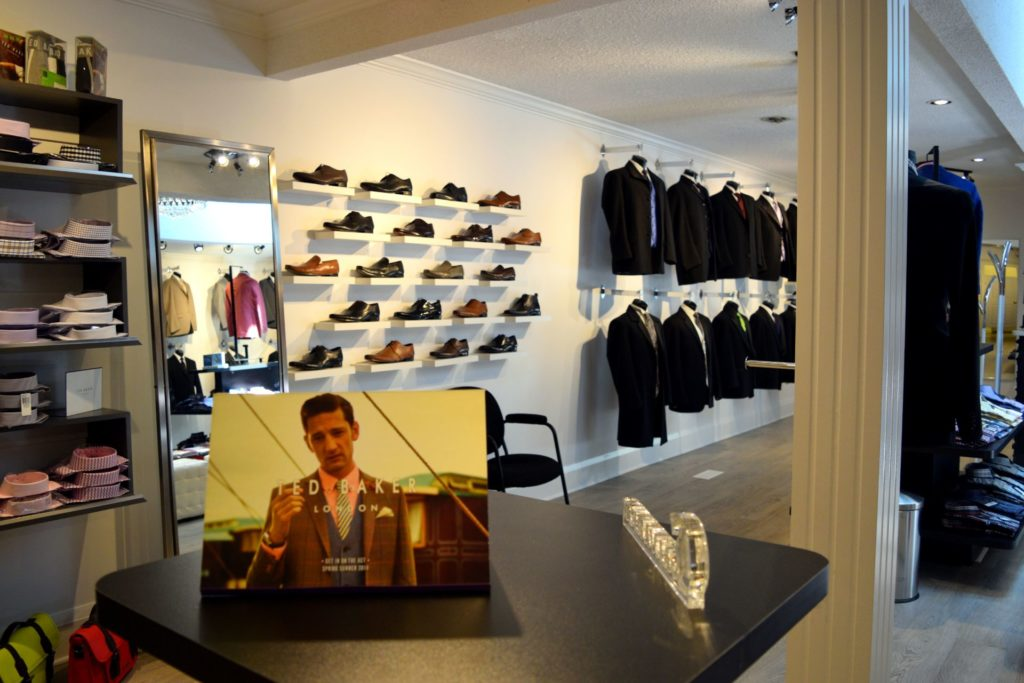 interior of menswear store with suits hung and shoes on display with lit up walls and posters