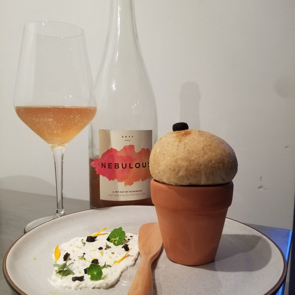 tasting menu dish with clay pot with pastry and sauce on side in front of glass of wine half poured from bottle in front of white wall