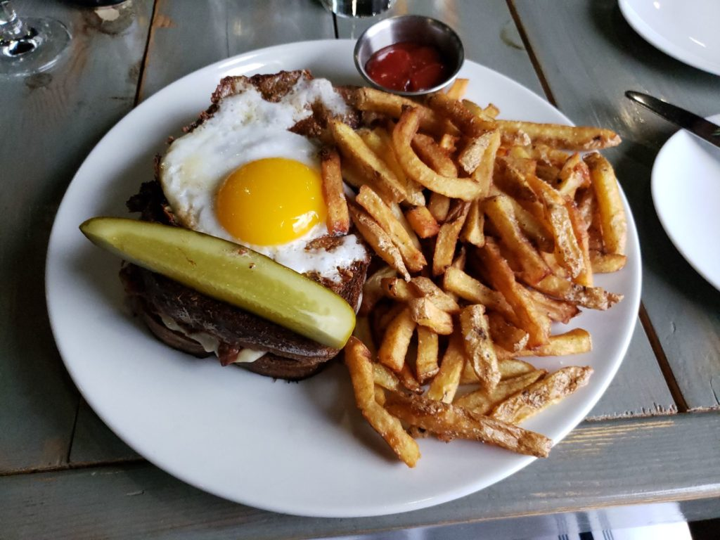 plate with hamburger with fried egg on top with pickle garnish and french fries with ketchup on the side