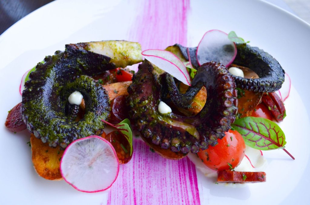 octopus entree plate with various coloured vegetables on white plate with decorative beet sauce smear on the bottom