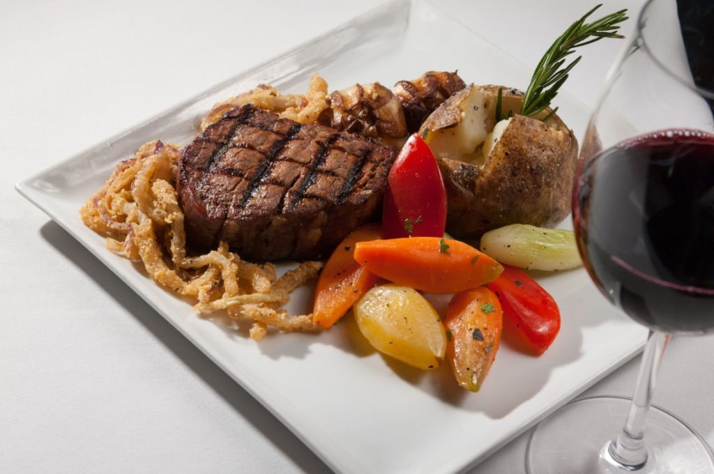 square plate of steak with fried onion and roasted vegetables on side with glass of red wine