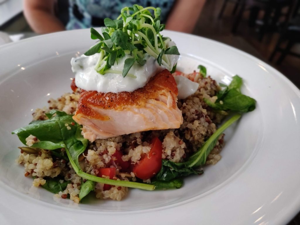 side view of salmon on white plate over a bed of quinoa and vegetables with micro green garnish