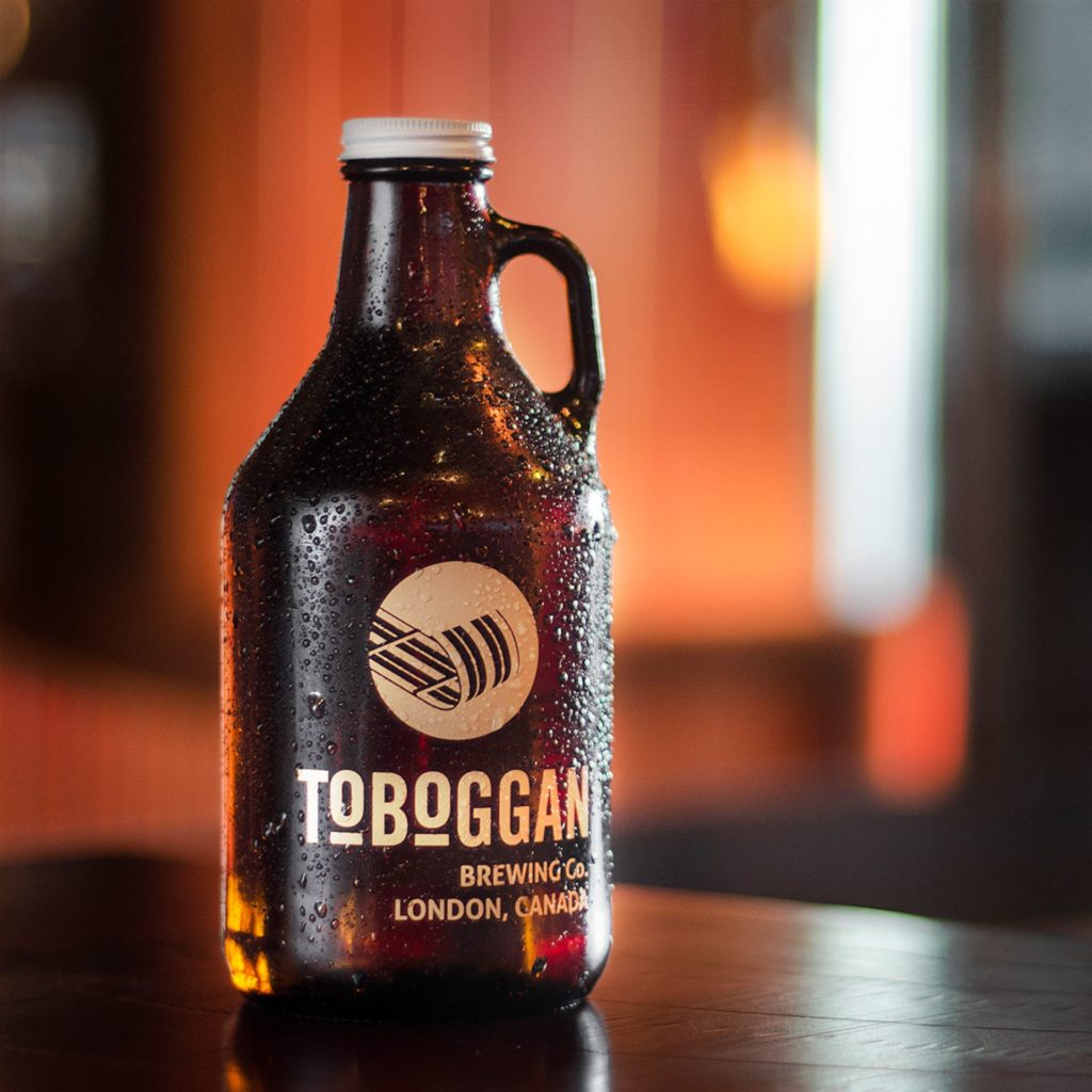 draught beer growler with logo on bottle on wooden table