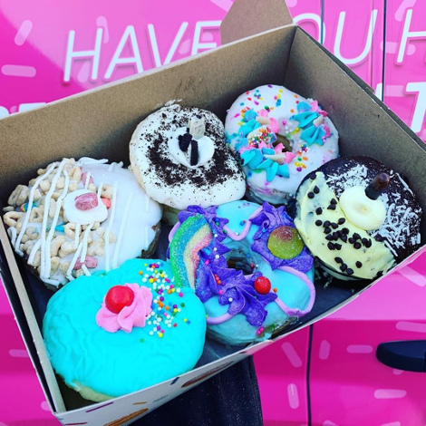 box of colourful donuts in front of bright pink background