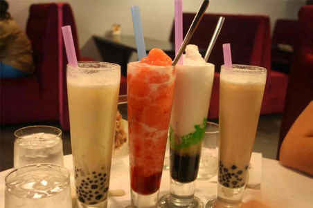4 tall bubble teas with straws on a counter with water beside