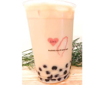single pink bubble tea in a branded to go cup with green herb prop in background