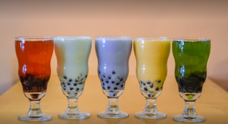 5 different coloured bubble teas in bulb glasses lined up on a counter