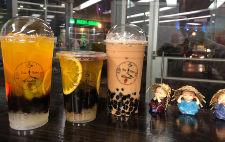 variety of bubble tea on dark counter beside 3 small asian figurines
