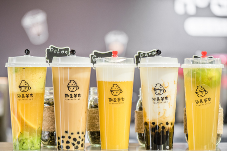 5 different yellow bubble teas in branded travel cups lined up