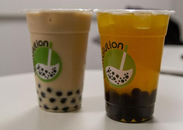 two different take out bubble teas beige and orange