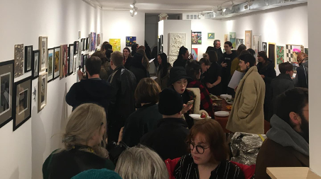 interior of busy art gallery with people looking at the art