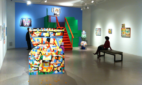 modern art display in studio with very bright colours and person sitting looking at art