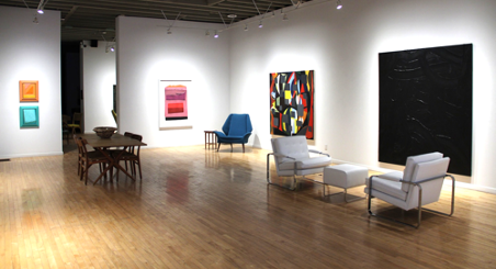 interior of gallery with various furniture in middle and pieces of art on the walls lit up