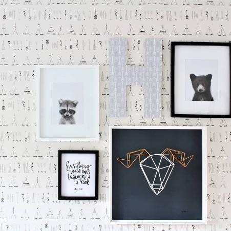 framed pictures of animals on display in store against patterned wallpaper