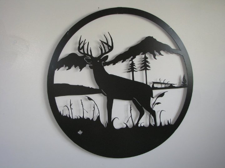 iron wall decor with a deer in the wilderness against a grey wall