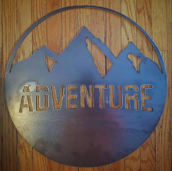 metal adventure sign with wood plank background