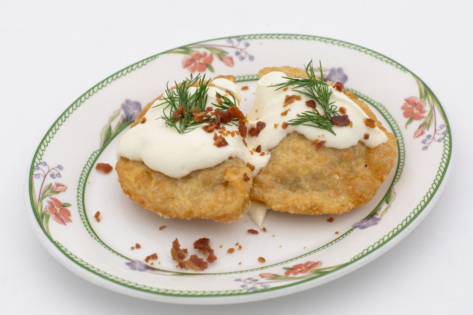 fried perogies on plate with sour cream drizzle bacon and green garnish on top