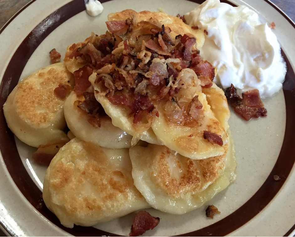 perogies with bacon and sour cream on the side on a white plate