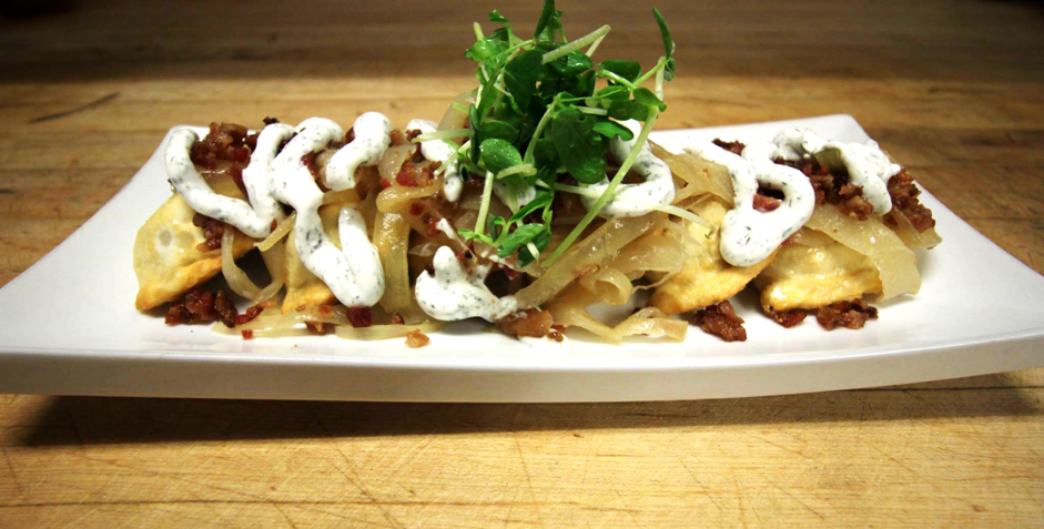 row of perogies with sour cream and bacon with a green garnish