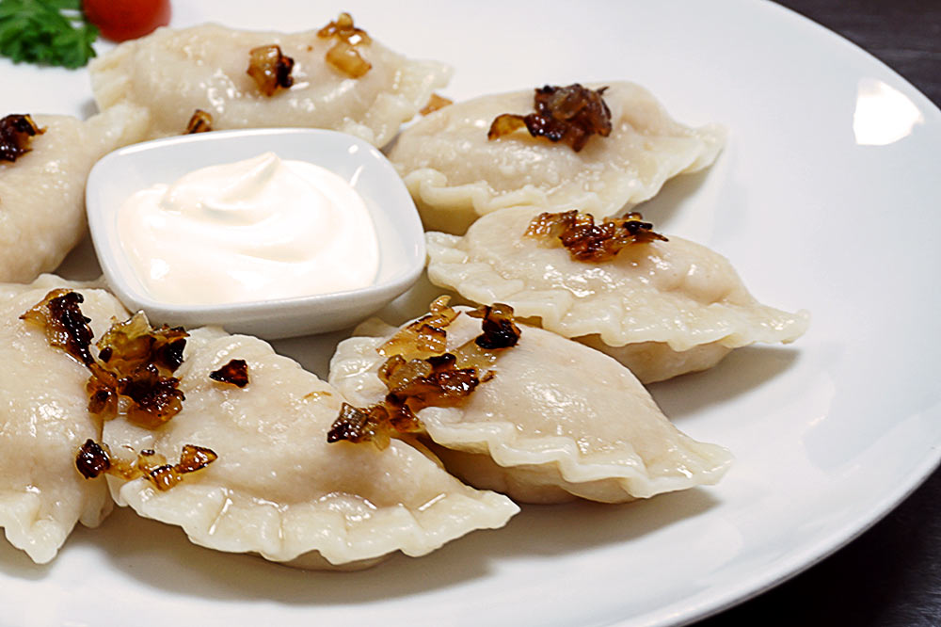 perogies with fried onions and sour cream ramekin in the centre