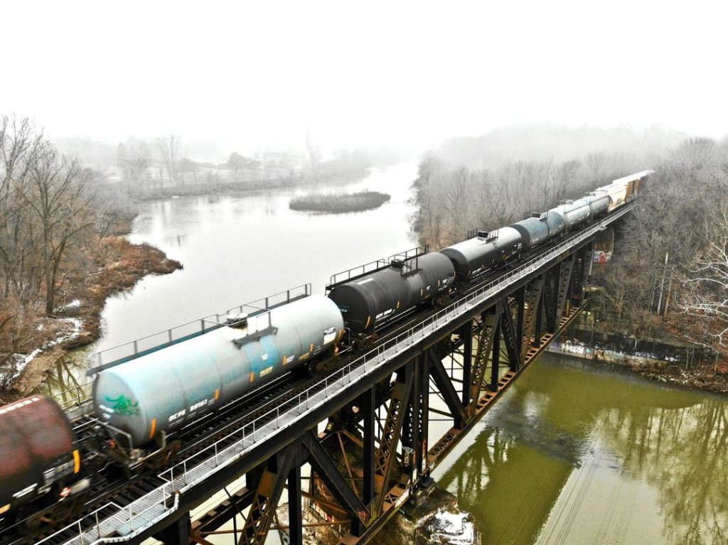aerial of train on bridge going over water on a foggy day