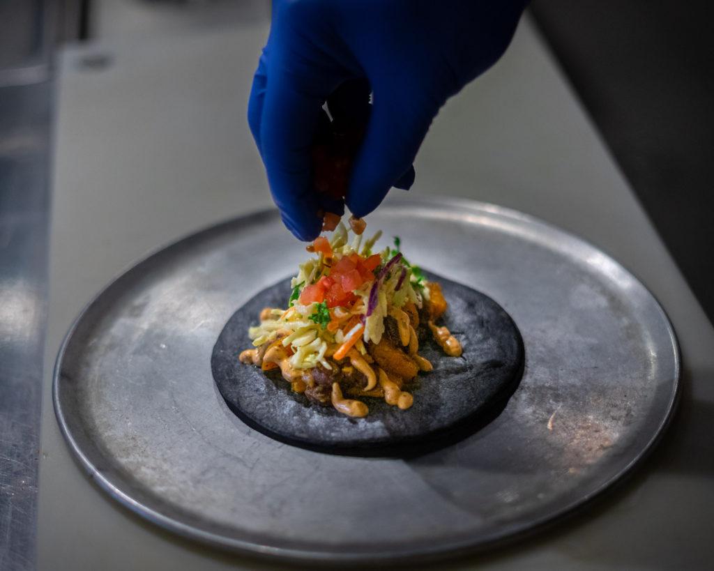 gloved hand putting garnish on top of tacos on black tortilla on metal circular sheet pan on counter