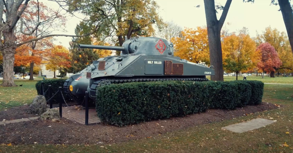 war tank statue in park in front of fall trees