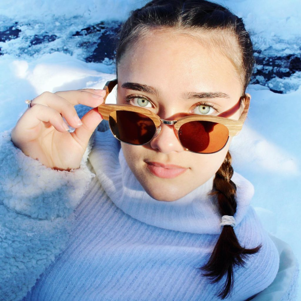 women in snow lowering sunglasses and looking at camera