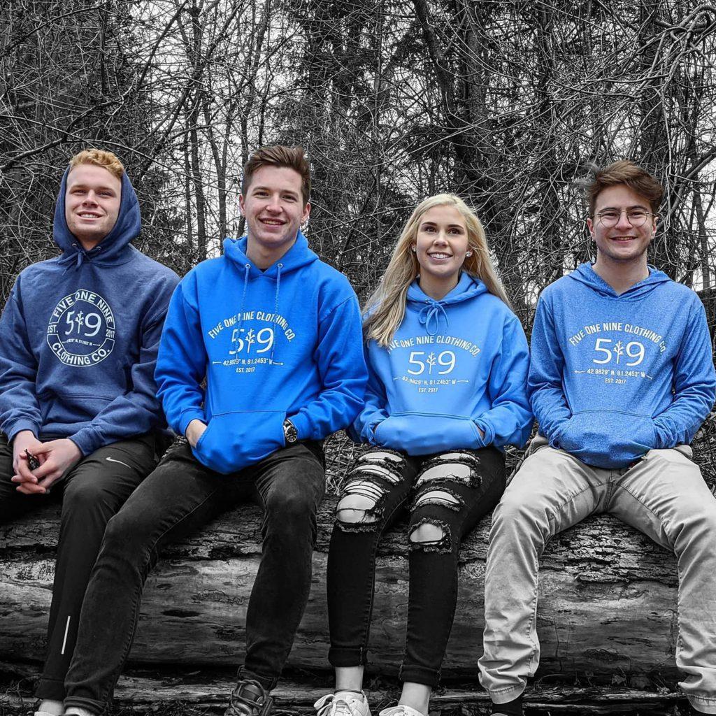 4 people sitting on log wearing matching blue sweaters