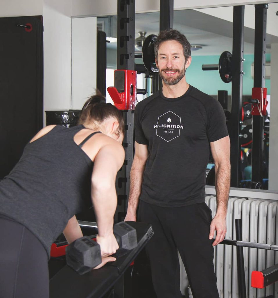 personal trainer male teaching rows to woman who is curling a weight