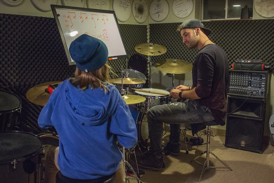 man teaching kid to play drums in studio with white board in front of them