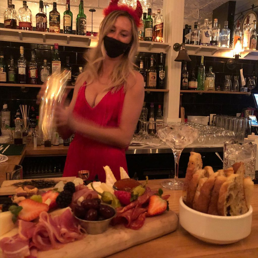 woman shaking cocktail in mixer at bar in devil costume