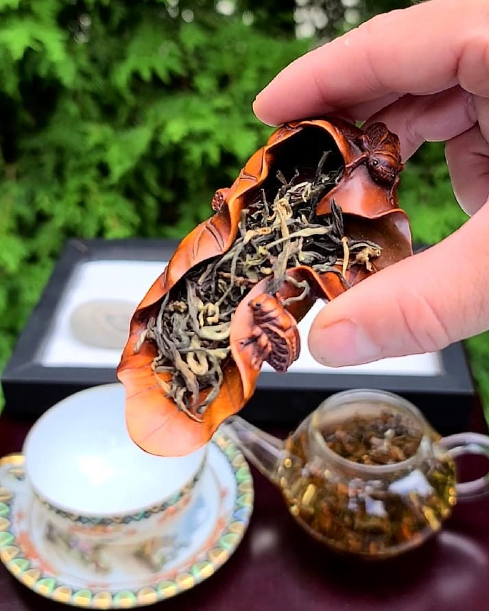 hand holding loose leaf tea in leather pouch above teacup on table
