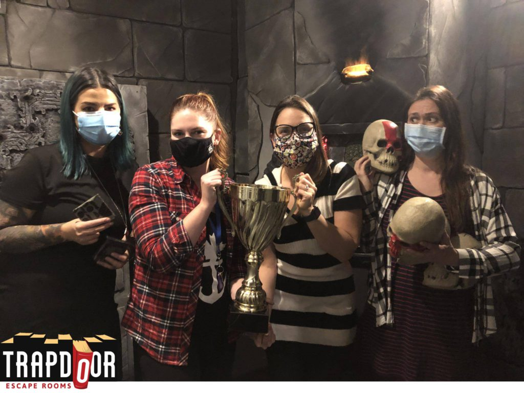 group of girls in a dark painted room wearing masks holding a trophy and skull props